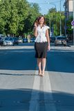 Pretty businesswoman walking on road Stock Images