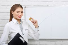 Pretty businesswoman wearing dress-code holds golden coin. Stock Image