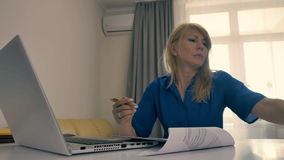 Pretty businesswoman working as freelancer with laptop at home. Pretty businesswoman is working on the laptop at home. Woman-freelancer is writing on the paper stock footage