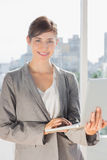 Pretty businesswoman working on laptop and smiling at camera Stock Photos