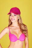 Pretty Busty Blonde In Bikini. Pretty young woman with full breasts wearing a bikini and matching pink cap, isolated on yellow Royalty Free Stock Photography