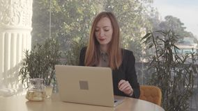 Adult businesswoman is working with laptop in her office, drinking ginger tea stock footage