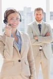 Pretty call centre agent with colleague behind her Stock Images