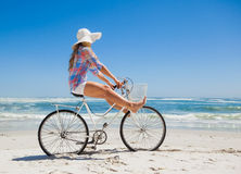 Pretty carefree blonde on a bike ride at the beach Stock Images