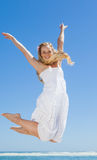 Pretty carefree blonde jumping and smiling at camera on the beach Stock Photo