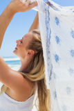 Pretty carefree blonde posing on the beach with scarf Stock Photography