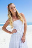 Pretty carefree blonde smiling at camera on the beach Stock Image
