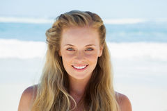 Pretty carefree blonde smiling at camera on the beach Stock Photos