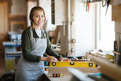 Pretty carpenter with spirit level. Portrait of pretty young carpenter in apron looking at camera with wide smile while holding spirit level on plank, blurred royalty free stock image