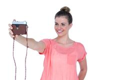 Pretty casual brunette taking a selfie with retro camera Stock Photos