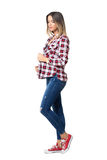 Pretty casual girl wearing jeans and sneakers posing and looking down. Royalty Free Stock Image