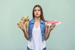 Pretty casual style girl with freckles got choosing sneakers or inconvenient but handsome shoes, and thinking. Stock Photo