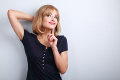 Pretty casual thinking woman woth finger under face looking up o Stock Images