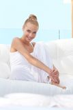 Pretty casual woman barefoot on sofa Royalty Free Stock Photography