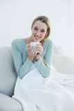 Pretty casual woman holding a cup sitting on couch under a blanket Royalty Free Stock Photos