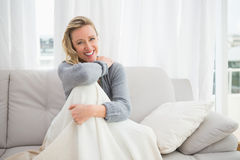 Pretty casual woman sitting on couch under a blanket Royalty Free Stock Photo