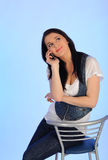 Pretty casual woman speaking on the phone. Sitting on the chair Royalty Free Stock Photo