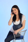 Pretty casual woman speaking on the phone. Sitting on the chair Stock Photography