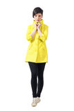 Pretty catwalk female model in yellow coat walking towards camera holding collar Stock Images