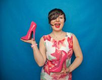 Pretty caucasian adult woman in white dress with flowers holding a pink Shoe with a very high heel on a blue solid Studio backgrou. Nd alone stock photography