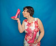 Pretty caucasian adult woman in white dress with flowers holding a pink Shoe with a very high heel on a blue solid Studio backgrou. Nd alone royalty free stock photography