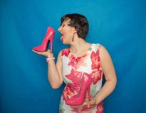 Pretty caucasian adult woman in white dress with flowers holding a pink Shoe with a very high heel on a blue solid Studio backgrou. Nd alone stock photos