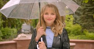 Pretty caucasian blonde student opens the umbrella preparing for rain being glad and optimistic in the green city park. Pretty caucasian blonde student opens stock footage