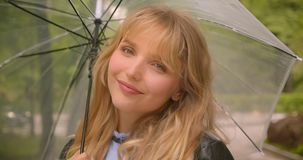 Pretty caucasian blonde student posing joyfully with umbrella into camera in the green city park. Pretty caucasian blonde student posing joyfully with umbrella stock video footage