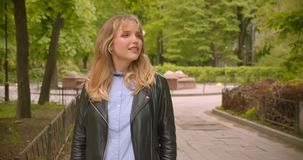 Pretty caucasian blonde student standing in the green park observing the beauty of nature. Pretty caucasian blonde student standing in the green park observing stock video footage