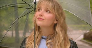 Pretty caucasian blonde student with umbrella smiling shyly into camera in the green city park. Pretty caucasian blonde student with umbrella smiling shyly into stock video footage