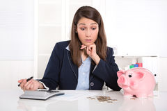 Pretty caucasian businesswoman in depression with piggy bank. Stock Photo