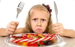 Pretty Caucasian female child eating dish full of candy in sweet sugar abuse dangerous diet Stock Image