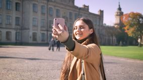 Pretty caucasian female is having video call and holding her phone in one hand while standing outdoor, urban background. City vibes, happy and relaxed in stock footage