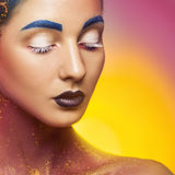 Pretty caucasian female with multicolor make up and closed eyes Royalty Free Stock Photos