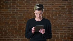 Pretty caucasian female with short hair is swiping her tablet while standing isolated next to brick wall in black. Sweater stock video