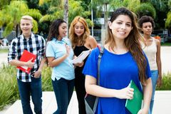 Pretty caucasian female student with group of international stud Stock Images