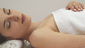 Girl closes her eyes on the massage table royalty free stock images
