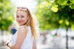 Pretty caucasian girl glance back. Portrait of pretty blond girl with sunglasses on head and white blouse loking back and smiling Stock Images