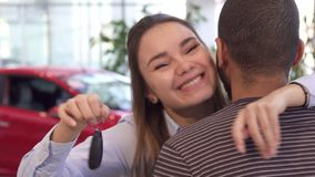 Girl hugs her boyfriend at the dealership. Pretty caucasian girl hugging her boyfriend at the dealership. Attractive young women showing car key over her man`s Stock Image