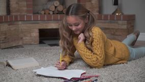 Pretty Caucasian girl with long ponytails laying at the soft carpet and drawing. Cute child resting at weekends at home stock video footage