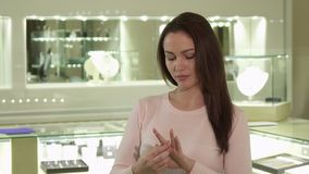 Girl looks at the ring on her finger at the jewelry shop. Pretty caucasian girl looking at the ring on her finger at the jewelry shop. Attractive brunette lady Stock Photo