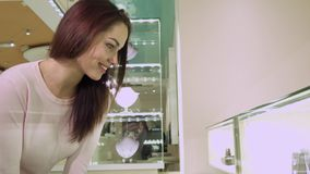 Girl looks at the shopping display with jewelry. Pretty caucasian girl looking at the shopping display with jewelry. Attractive young woman bending over showcase Royalty Free Stock Photos
