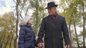 Pretty Caucasian girl in white warm hat spending weekends with her grandfather. Child jumping around senior smiling man. In elegant black hat and coat stock video footage