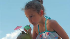 Pretty caucasian little girl in a swimsuit on the beach against the blue sky, drinking with a tube of coconut drink. Pretty caucasian little girl curly hair stock video footage