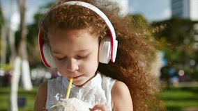 Pretty caucasian little girl curly hair listening to music in white headphones and drinking coconut. stock video