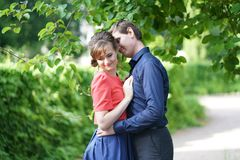 Pretty caucasian love couple walking in the green summer park, having smiles, kisses and hugs stock photography