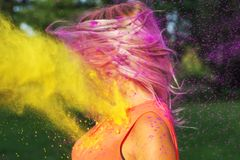 Pretty caucasian model with fluttering hair in wind playing with. Pretty caucasian woman with fluttering hair in wind playing with dry paint Holi stock photos