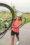 Pretty Caucasian Sportswoman Works Out with Bicycle Outside Stock Photos