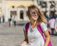 Girl sunglasses wind sun smile. Pretty caucasian tourist girl is looking at the map in the old city center location, sunny day Royalty Free Stock Image