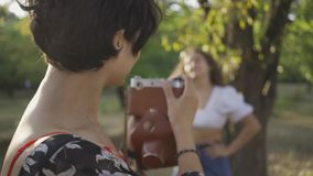 Pretty caucasian woman with curly hair posing in background while her friend taking a photo using old camera in. Attractive caucasian woman with curly hair stock video footage